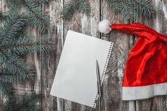 Η επιστολή Χαρούμενα Χριστούγεννας με το καπέλο santa ` s και το πράσινο έλατο διακλαδίζεται στο παλαιό ξύλινο υπόβαθρο Στοκ φωτογραφία με δικαίωμα ελεύθερης χρήσης