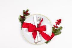 Η επιτραπέζια θέση Χριστουγέννων που θέτει με το πιάτο, μαχαιροπήρουνα, πεύκο διακλαδίζεται, κορδέλλα και κόκκινα μούρα Στοκ Φωτογραφίες