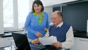 Η επιτυχής αγορά συνταξιούχων, ανώτερο ζεύγος με την πιστωτική κάρτα εξετάζει το lap-top και χαίρεται απόθεμα βίντεο