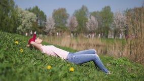 Η επιτυχής επιχειρησιακή γυναίκα απολαμβάνει το ελεύθερο χρόνο ελεύθερου χρόνου της σε ένα πάρκο με τα ανθίζοντας δέντρα κερασιών απόθεμα βίντεο
