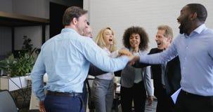 Η επιτυχής ομάδα επιχειρηματιών ενώνει τα χέρια μαζί, ομάδα φυλών μιγμάτων του ευτυχούς χαμόγελου επαγγελματιών στο σύγχρονο γραφ απόθεμα βίντεο