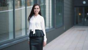 Η επιτυχής όμορφη επιχειρησιακή γυναίκα περπατά κοντά στο κέντρο γραφείων, σε αργή κίνηση φιλμ μικρού μήκους
