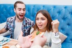 Η επιχείρηση κάθεται σε έναν καφέ, κάποιος δίνει στο κορίτσι μια πίτσα, ο τύπος στα γέλια υποβάθρου Στοκ φωτογραφία με δικαίωμα ελεύθερης χρήσης