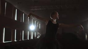 Η επιχείρηση μπαλέτου Prima σε ένα σκοτεινό φόρεμα σε μια σκοτεινή σκηνή θεάτρων που προετοιμάζει στον καπνό εκτελεί τις κινήσεις φιλμ μικρού μήκους