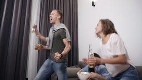 Η επιχείρηση των νέων φίλων προσέχει τον αγώνα στη TV tensely, εκφράζει τις συγκινήσεις τους λαμπρά, σημειώνοντας τη νίκη του του απόθεμα βίντεο