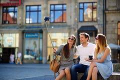 Η επιχείρηση των νέων φίλων φωτογραφίζεται στο τετράγωνο πόλεων στοκ εικόνα