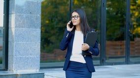 Η επιχειρηματίας έχει τη συνομιλία που χρησιμοποιεί το κινητό τηλέφωνο Το επιχειρησιακό κορίτσι στα γυαλιά και το επίσημο κοστούμ απόθεμα βίντεο