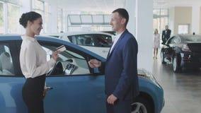 Η επιχειρηματίας δίνει μια πιστωτική κάρτα στο διευθυντή στη εμπορία αυτοκινήτων φιλμ μικρού μήκους