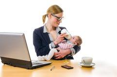 Η επιχειρηματίας δίνει στο μωρό το μπουκάλι Στοκ φωτογραφίες με δικαίωμα ελεύθερης χρήσης