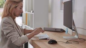 Η επιχειρηματίας απασχολείται στο σπίτι στο γραφείο απόθεμα βίντεο