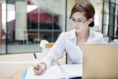 Η επιχειρηματίας γράφει σε ένα έγγραφο Στοκ Εικόνα