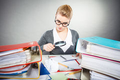 Η επιχειρηματίας εξερευνά τα έγγραφα με το μεγάλο loupe Στοκ Φωτογραφία