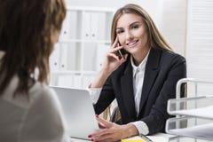 Η επιχειρηματίας εξετάζει τη κάμερα Ο συνάδελφός της κοιτάζει Στοκ Εικόνες