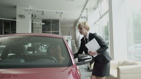 Η επιχειρηματίας επιθεωρεί μια καμπίνα αυτοκινήτων ` s στην αίθουσα εκθέσεως αυτοκινήτων απόθεμα βίντεο