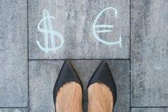 Η επιχειρηματίας επιλέγει τα σημάδια ευρώ ή δολαρίων στοκ εικόνες