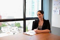 Η επιχειρηματίας κάθεται και γράφει την επιχειρησιακή διαδικασία σε χαρτί στοκ φωτογραφία