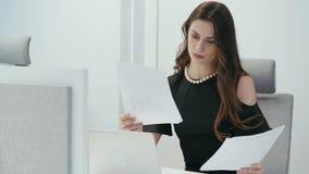 Η επιχειρηματίας κάθεται στο γραφείο με τον υπολογιστή και ελέγχει τα έγγραφα απόθεμα βίντεο