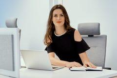 Η επιχειρηματίας κάθεται στο γραφείο με τον υπολογιστή και το ημερολόγιο Στοκ φωτογραφία με δικαίωμα ελεύθερης χρήσης