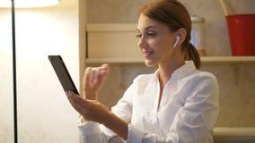 Η επιχειρηματίας κάνει την τηλεοπτική κλήση, smartphone χρήσης και earpods απόθεμα βίντεο