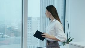 Η επιχειρηματίας κρατά το ημερολόγιο σε ένα γραφείο γυαλιού απόθεμα βίντεο