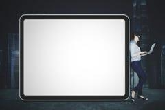 Η επιχειρηματίας κλίνει στον κενό πίνακα διαφημίσεων Στοκ Εικόνα