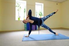 Η επιχειρηματίας μελετά τις βασικές ασκήσεις γιόγκας στη σε απευθείας σύνδεση σειρά μαθημάτων στοκ φωτογραφία