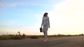 Η επιχειρηματίας με έναν μαύρο χαρτοφύλακα περπατά στο ελαφρύ κοστούμι και τους άσπρους ψηλοτάκουνους περιπάτους παπουτσιών κατά  απόθεμα βίντεο