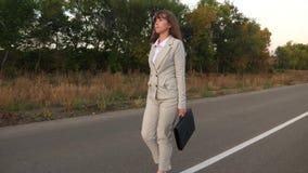 Η επιχειρηματίας με έναν μαύρο χαρτοφύλακα περπατά στο ελαφρύ κοστούμι και τους άσπρους ψηλοτάκουνους περιπάτους παπουτσιών κατά  φιλμ μικρού μήκους