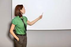 Η επιχειρηματίας με παραδίδει τις τσέπες δείχνοντας στο whiteboard στην αρχή Στοκ φωτογραφία με δικαίωμα ελεύθερης χρήσης