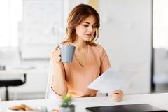 Η επιχειρηματίας με τα έγγραφα πίνει τον καφέ στο γραφείο Στοκ Εικόνα