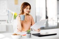 Η επιχειρηματίας με τα έγγραφα πίνει τον καφέ στο γραφείο Στοκ εικόνα με δικαίωμα ελεύθερης χρήσης