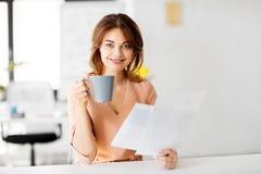 Η επιχειρηματίας με τα έγγραφα πίνει τον καφέ στο γραφείο Στοκ φωτογραφία με δικαίωμα ελεύθερης χρήσης