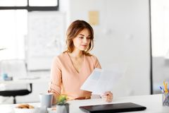 Η επιχειρηματίας με τα έγγραφα πίνει τον καφέ στο γραφείο Στοκ Φωτογραφία