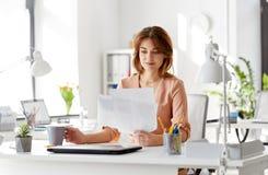 Η επιχειρηματίας με τα έγγραφα πίνει τον καφέ στο γραφείο Στοκ Φωτογραφίες