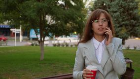 Η επιχειρηματίας με τα γυαλιά στο ελαφρύ κοστούμι περπατά στον καφέ κατανάλωσης πάρκων και ομιλία σε ένα smartphone απόθεμα βίντεο