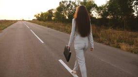 Η επιχειρηματίας με τη μακριά σκοτεινή τρίχα φέρνει στο χέρι της το μαύρο χαρτοφύλακα, περίπατοι γυναικών κατά μήκος της ασφάλτου φιλμ μικρού μήκους