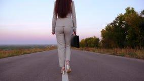 Η επιχειρηματίας με το μαύρο χαρτοφύλακα στο χέρι της πηγαίνει στα εσώρουχα και το λευκό υψηλό έβαλε τακούνια στα παπούτσια στην  απόθεμα βίντεο