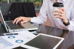 Η επιχειρηματίας με το φορητό προσωπικό υπολογιστή & η οικονομική συνοπτική γραφική παράσταση κάθονται Στοκ εικόνες με δικαίωμα ελεύθερης χρήσης