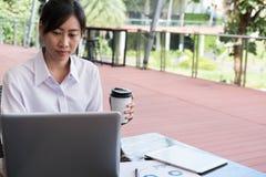 Η επιχειρηματίας με το φορητό προσωπικό υπολογιστή & η οικονομική συνοπτική γραφική παράσταση κάθονται Στοκ Εικόνες