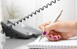 Η επιχειρηματίας μιλά στο τηλέφωνο και παίρνει τις σημειώσεις Στοκ Φωτογραφίες
