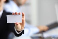Η επιχειρηματίας παρουσιάζει κενή κάρτα, καθμένος στο γραφείο Στοκ εικόνα με δικαίωμα ελεύθερης χρήσης