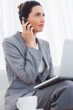 Η επιχειρηματίας που καλεί με το κινητό τηλέφωνό της και που χρησιμοποιεί το lap-top κάθεται Στοκ φωτογραφία με δικαίωμα ελεύθερης χρήσης