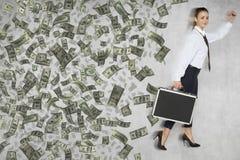 Η επιχειρηματίας σε μια βιασύνη χάνει τα χρήματα από μια βαλίτσα στοκ φωτογραφία