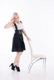 Η επιχειρηματίας στέκεται κοντά σε μια καρέκλα Στοκ Εικόνες