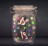 Η επιχειρηματίας συνέλαβε σε ένα βάζο γυαλιού με τα ζωηρόχρωμα app εικονίδια γ Στοκ Εικόνες