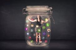 Η επιχειρηματίας συνέλαβε σε ένα βάζο γυαλιού με τα ζωηρόχρωμα app εικονίδια γ Στοκ Φωτογραφίες