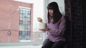 Η επιχειρηματίας τρώει τα στιγμιαία νουντλς καθμένος στο windowsill ενάντια στο κτήριο τούβλου φιλμ μικρού μήκους