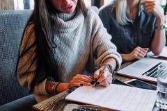 Η επιχειρηματίας υπογράφει μια σύμβαση σε έναν καφέ σε έναν ξύλινο πίνακα στοκ φωτογραφία