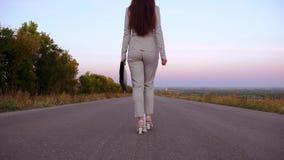 Η επιχειρηματίας φέρνει το μαύρο χαρτοφύλακα στο χέρι της, περίπατοι γυναικών κατά μήκος της ασφάλτου έξω από την πόλη που φορά τ απόθεμα βίντεο