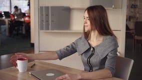 Η επιχειρηματίας throughs με το στενό lap-top προγράμματος και απολαμβάνει το φλυτζάνι του τσαγιού φιλμ μικρού μήκους